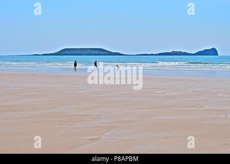 Ein paar Urlauber zu Fuß ihren Hund entlang der Küste am Strand von Llangennith gegen Würmer Kopf, Rhossili Bay, Gower, s. Wales - Stockfoto