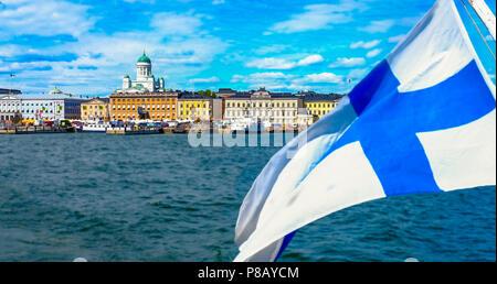 Skyline von Helsinki aus dem Meer. Die finnische Flagge schwimmt. Marktplatz und Helsinki-Kathedrale vom Meer. Die seekape von Helsinki im Sommer. - Stockfoto