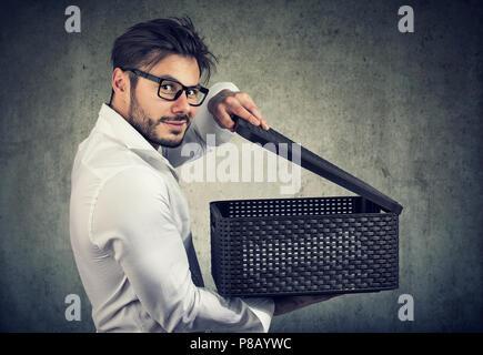 Sly Ränkeschmied Holding und Öffnen einer und Suchen mit Grinsen an der Kamera, während auf Grau posieren. - Stockfoto