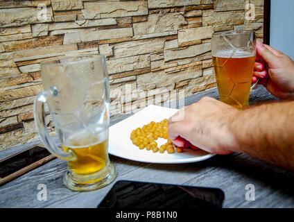 Freunde sitzen in einer Bar. Männer Hände halten ein Glas Bier. - Stockfoto