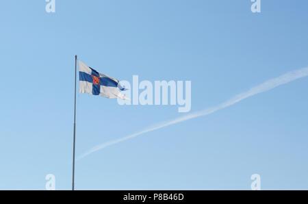 Staat Fahne von Finnland fliegt von einem Fahnenmast gegen einen hellblauen Himmel mit einem einzigen Kondensstreifen - Stockfoto