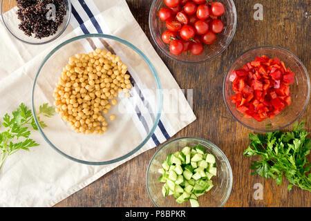 Superfood Konzept. Zutaten zum kochen vegetarisch Salat mit Kichererbsen, schwarz Quinoa und Gemüse auf Holztisch, Ansicht von oben - Stockfoto