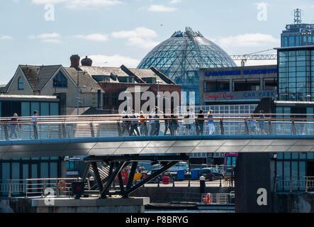 Menschen die Lagan Wehr Fußgänger- und Zyklus Brücke, Belfast Kreuzung. Das Glas anzeigen Dome am Victoria Square kann im Hintergrund gesehen werden. - Stockfoto