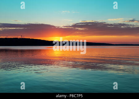 Wunderschöne orange teal Sonnenuntergang auf großen ruhigen See - Stockfoto