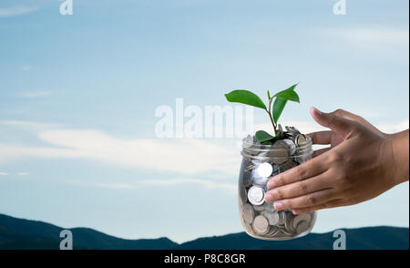 Die Hand von der Frau hält ein Glas mit Münzen und pflanzen auf den Berg und blauer Himmel mit Kopie Raum in Konzept und unscharfen Hintergrund - Stockfoto