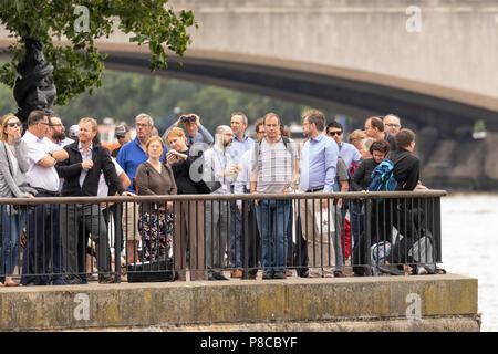 London, Großbritannien. 10. Juli 2018. Menschen versammeln sich entlang der Themse der RAF 100 Flypast in London am 10. Juli 2018 Kredit zu beobachten: Nick Whittle/Alamy leben Nachrichten - Stockfoto