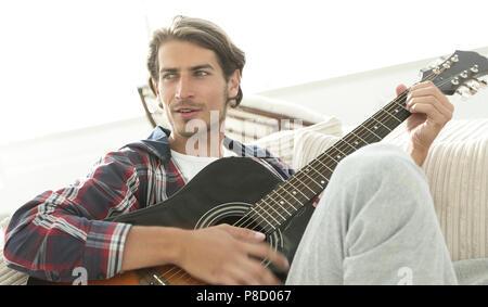 Moderne Kerl mit Gitarre sitzt auf einem Sofa im Wohnzimmer. - Stockfoto