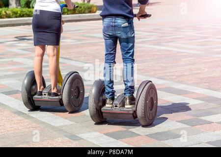 Paar in Freizeitkleidung, moderne Gyro scooter hover Board im City Straße auf hellen, sonnigen Tag. Elektrisches eco-Zukunft städtischer Verkehr Gadget. - Stockfoto