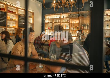 Lächelnden jungen Freunden in einer Bar zusammen zu sitzen