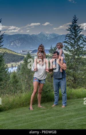 Attraktive, Verspielt, lässig Family Portrait von Eltern und zwei kleinen Töchtern. Hat jeder Elternteil Kind auf sholders, in einem im Freien. Model Release - Stockfoto