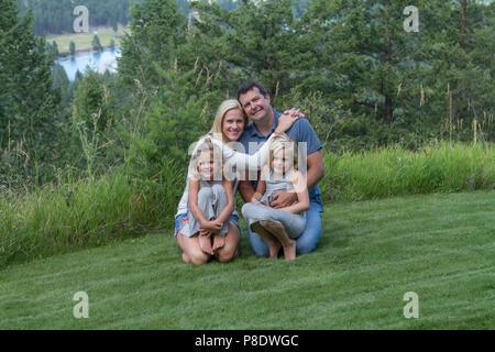 Outdoor Familie Portrait von Eltern und zwei Töchter. Casual, verspielten in grüner Umgebung. Model Released - Vati Nr. 116, Mädchen auf #114, Mädchen auf Rig links - Stockfoto