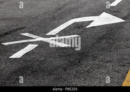 Rechts ist verboten. Weißer Pfeil, Fahrbahnmarkierung auf dunklen Asphalt gekreuzt. Nahaufnahme mit selektiven Fokus