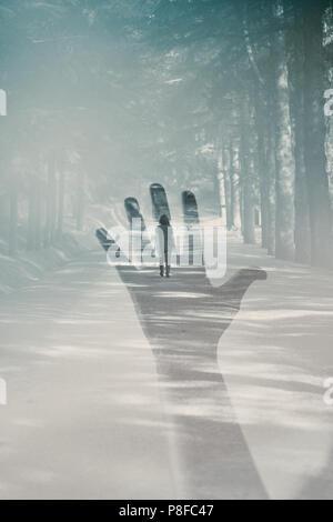Double Exposure der Hand einer Frau, die für eine Frau, die auf einem Wanderweg in den Wald - Stockfoto