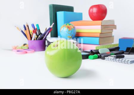 Vordergrund ein grüner Apfel auf dem Hintergrund von Schulmaterial. Foto mit Kopie Raum - Stockfoto