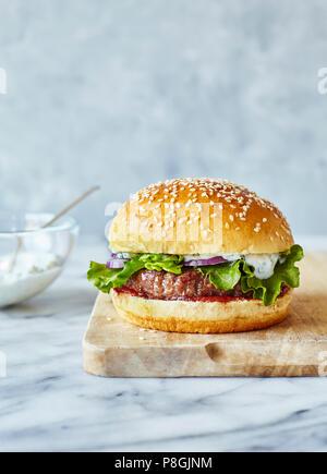 Lamm Burger in brioche Brötchen mit Minze Joghurt, serviert auf einem Holzbrett - Stockfoto