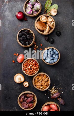 Sortiment raw Organic lila Zutaten: Auberginen, Artischocken, Kartoffeln, Zwiebeln, Beeren, Nüsse, Karotten, Rosenkohl, Trauben über dunkle Hinterg - Stockfoto