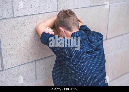 Jugendlich in gefalteten Armen gegen die Wand und schrie. - Stockfoto