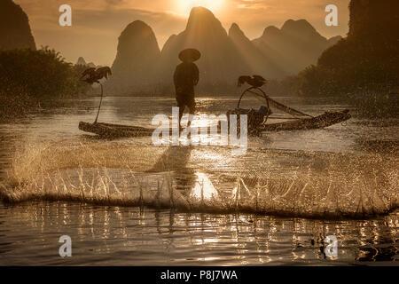 Kormoran Fischer casting Netz auf dem Li Fluss, Xingping, Guilin China, als die Sonne hinter dem karstgebirge hinter ihm setzt. - Stockfoto