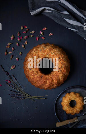 Nussbaum und Karotte Pound Cake mit trockenen Rosen und Lavendel. Schwarzer Hintergrund, Ansicht von oben - Stockfoto