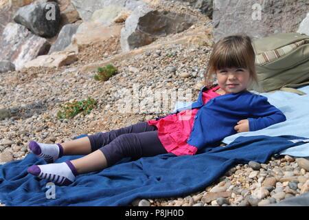 Kleinkind Mädchen auf blauen Handtuch hinlegen Entspannen am Strand. - Stockfoto