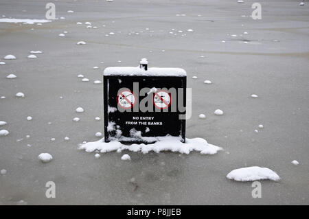 Keinen Eintrag Warnschild in einem gefrorenen Teich an einem kalten, winterlichen, verschneiten Tag, Hampstead Heath in NW-London, England, Großbritannien - Stockfoto