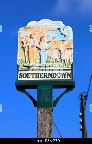 Southerndown Ortsschild hoch oben auf einem Post neben dem Pfad und Hauptstraße durch das Dorf, Tiere und Besucher. - Stockfoto