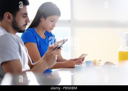 Partner mit Telefon, während Zusammen essen Frühstück - Stockfoto