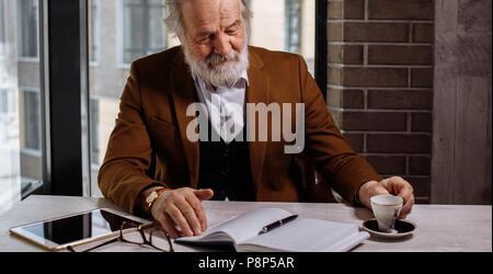 Nahaufnahme 7/8 Foto von älteren Geschäftsmann Trinken einer Tasse Kaffee während der Arbeit - Stockfoto