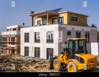 Ein neues Gebäude neben einem Shell in einem Baustellenbereich mit einem Radlader im Vordergrund | Verwendung weltweit - Stockfoto
