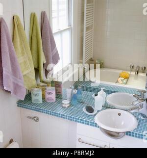 Blass Grün Und Lila Bettwäsche Neben Verspiegelte Wand über Dem Waschbecken  In Blau Mosaik Fliesen