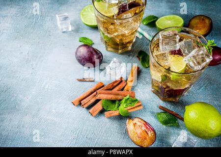 Sommer iced Erfrischung trinken. Zimt und Pflaume Limonade Cocktail mit frischen, Limette und Minze, blauer Hintergrund Kopie Raum - Stockfoto