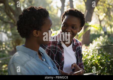 Zwillinge Geschwister mit Handy beim Entspannen auf der Werkbank - Stockfoto