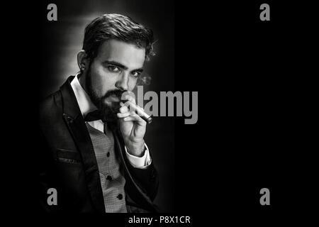 Schwarz-weiß-Porträt von bärtigen rauchen Zigarre Herrn im Anzug auf der Kamera posieren - Stockfoto
