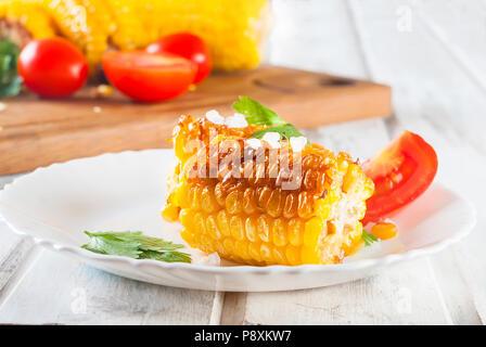 Leckere gegrillte Maiskolben mit Kräutern, Gemüse und Salz auf eine weisse Platte und eine weiße Holztisch - Stockfoto
