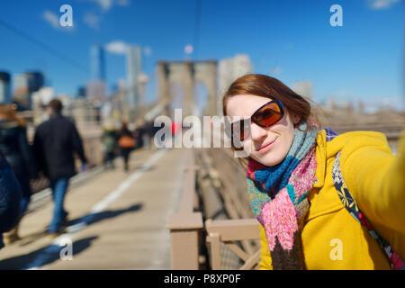 Schöne junge Frau eine selfie mit Ihrem Smartphone auf der Brooklyn Bridge, New York, am sonnigen Frühlingstag - Stockfoto