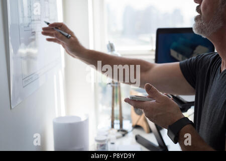 Mann mit Handy während Tabelle suchen - Stockfoto