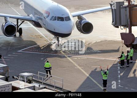 Berlin, Deutschland, Ramp Agent legt einen British Airways Flugzeuge auf dem Vorfeld des Flughafen Berlin Tegel in der Parkposition - Stockfoto