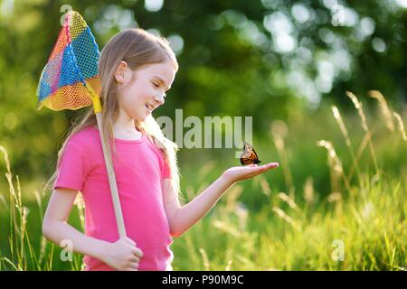 Süße kleine Mädchen fangen Schmetterlinge und Käfer mit ihrer Schaufel-net auf schönen sonnigen Sommertag - Stockfoto