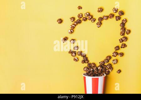 Süße Schokolade Popcorn in Papier gestreift weiß rot Tasse. - Stockfoto