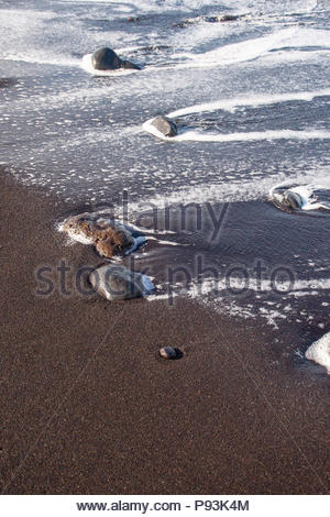 Weißer Schaum auf schwarzer Sand an einem Strand in Puerto de la Cruz, Teneriffa, Kanarische Inseln, Spanien - Stockfoto