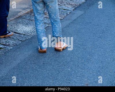 Frau, die traditionelle japanische Sandalen mit Jeans auf der Straße - Stockfoto