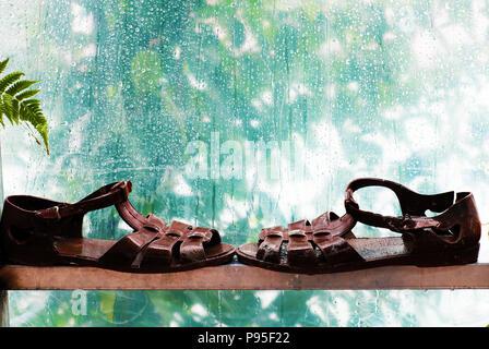 Paar Badeschuhe neben auf Fenster mit regnerischen Hintergrund, Regen fällt im regnerischen Tag, cyan Farbe ist schön und Kunstszene - Stockfoto