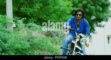 Junger Mann sitzt auf einem Motorrad im Freien - Stockfoto