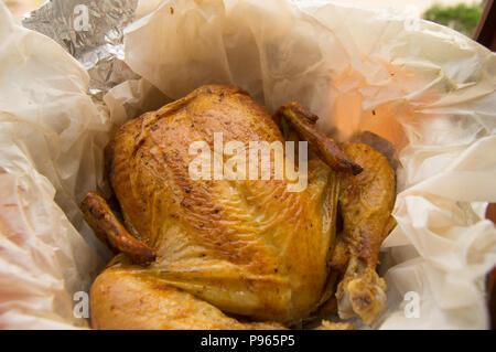 Gegrillte ganzes Huhn mit knusprigen goldenen Haut auf weißem Pergament, Ansicht von oben, close-up - Stockfoto