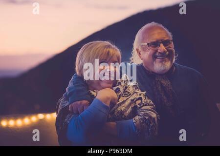 Mann und Frau senior Herren gealtert in Liebe umarmen und Spaß auf der Dachterrasse im Urlaub zu Hause Lächeln haben. Nacht Licht Atmosphäre für romantische Szene. t - Stockfoto