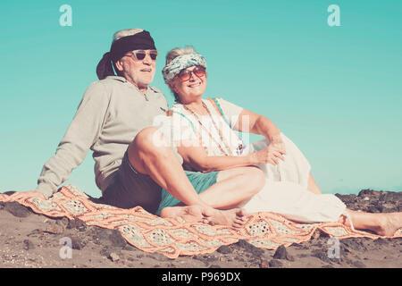 Paar der älteren kaukasischen Hippie style und das Leben auf dem felsigen Strand auf Teneriffa. Farben und alternativen Lebensstil für Totally Freiheit Konzept in der Nähe von - Stockfoto