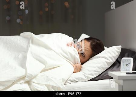 Angst Frau versteckt unter Decke lag auf einem Bett in der Nacht zu Hause - Stockfoto
