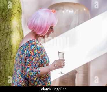 Eine Dame mit einem rosa Perücke und einem Glas Prosecco bei Latitude Festival, henham Park, Suffolk, England, 15. Juli 2018 - Stockfoto