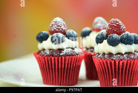 Makro Nahaufnahme von Red velvet Cupcakes mit Früchten dekoriert und Abstauben mit Süßwaren Zucker. - Stockfoto