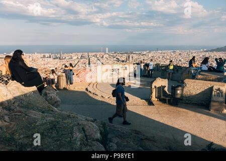Touristen und Einheimische sammeln die Ansicht der Stadt Barcelona aus dem Karmel Bunker bei Sonnenuntergang an einem heißen Sommerabend zu bewundern. - Stockfoto